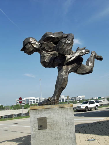 Pitcher sculpture in front of ball park entrance.